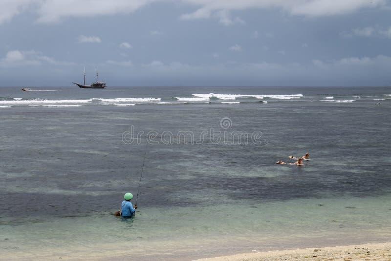 Fiskare och surfare p? den Serangan stranden arkivfoto