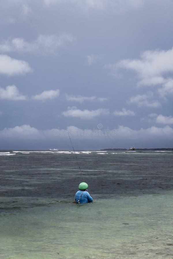 Fiskare och surfare p? den Serangan stranden royaltyfria bilder