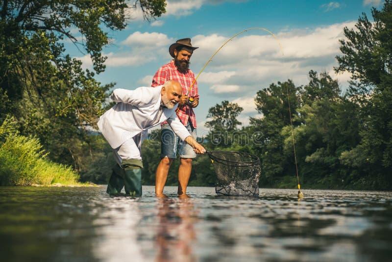Fiskare- och troféforell Lyckligt familjbegrepp - fader och son tillsammans Flyga stången och rullen med en brun forell från a arkivbilder
