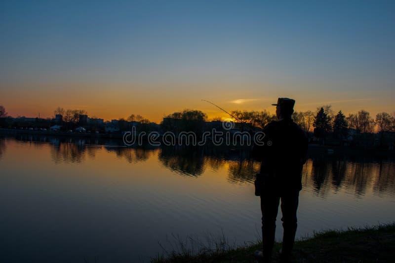 Fiskare på den mörka floden arkivfoto