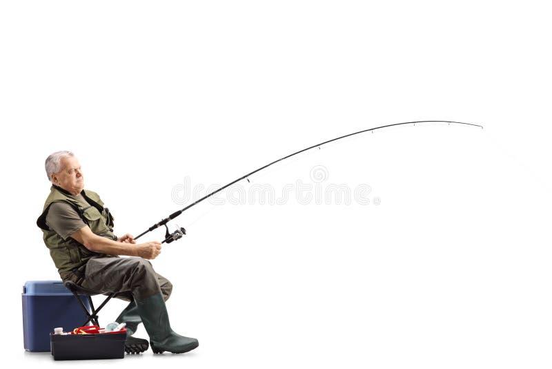 Fiskare på en stol med en metspö som väntar på ett lås fotografering för bildbyråer