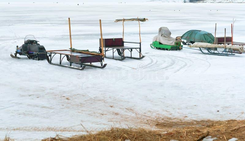 Fiskare på isen som är klar att gå i den elektriska släden som är ytterligare från kusten, snövesslor för vinterfiske fotografering för bildbyråer