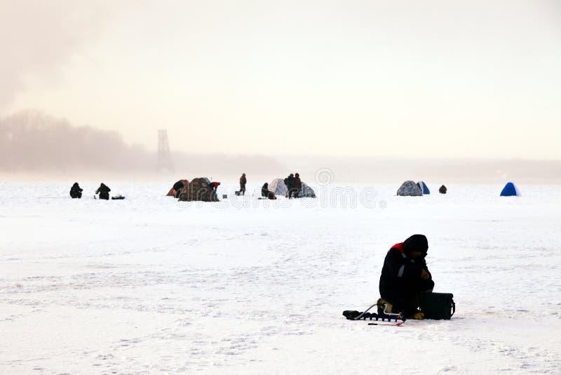 Fiskare på vinterfiske med tältlåsfisken på isen Begrepp av den manliga hobbyen, sport, passion, helg i natur arkivbilder