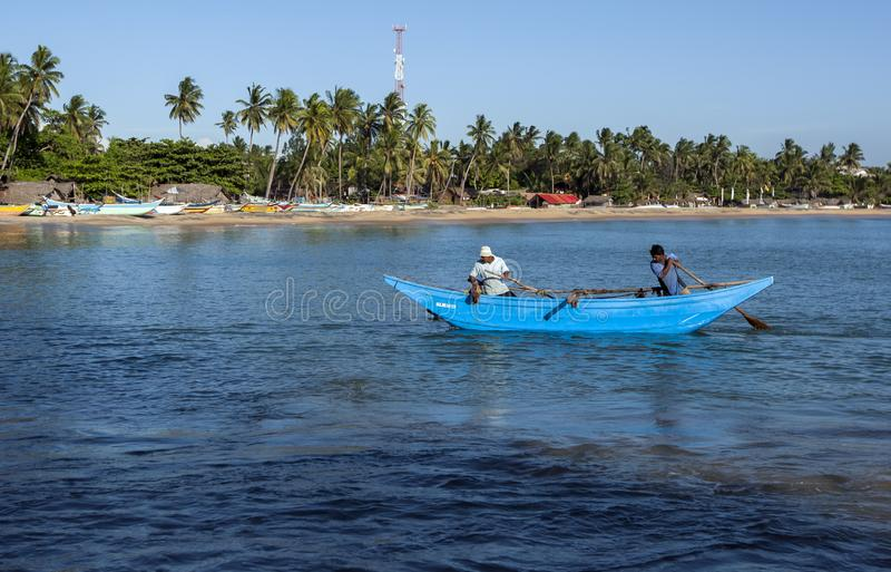 Fiskare paddlar deras utriggarefartyg royaltyfri fotografi