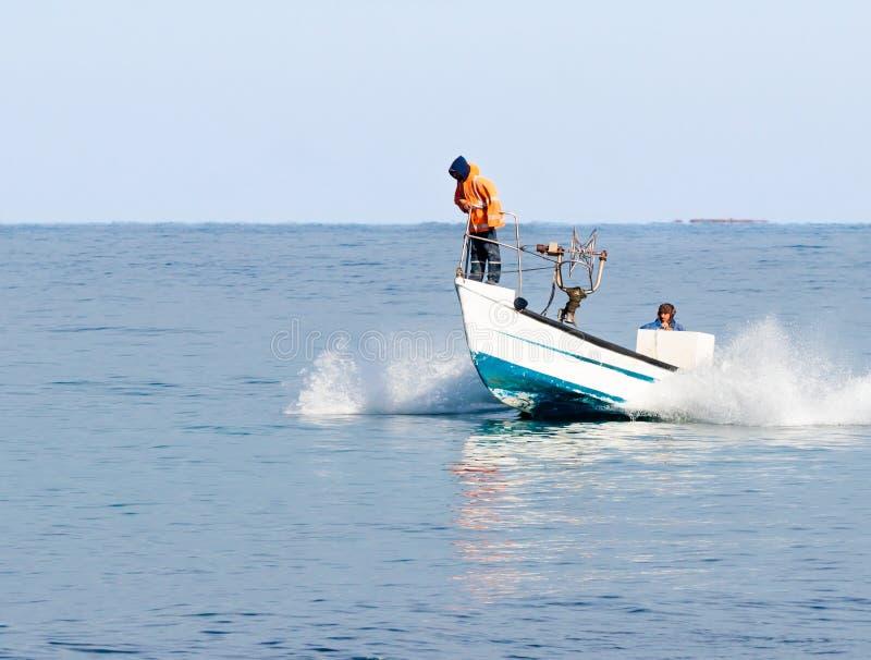 Fiskare patrullerar på fartyget och söka efterfisken royaltyfri bild