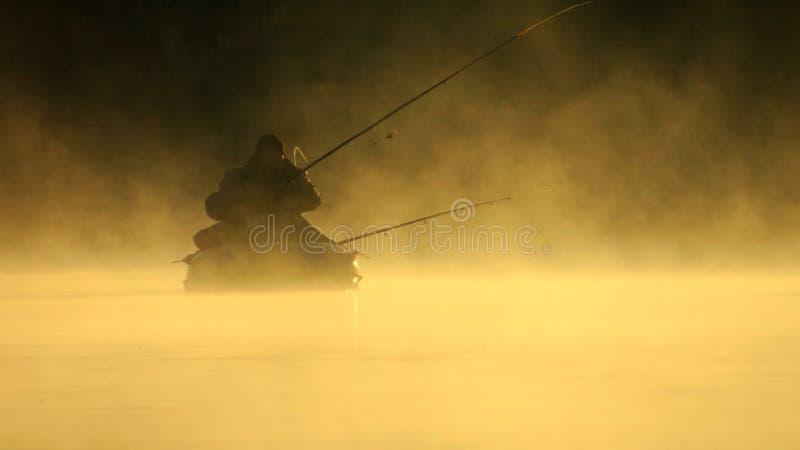 Fiskare Silhouette dimmig morgon för höst arkivbild
