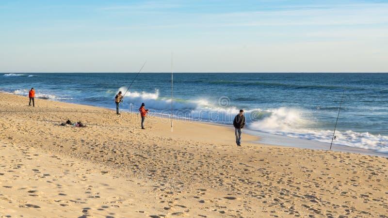 Fiskare som fiskar på stranden på Faro, Algarve, Portugal royaltyfri fotografi