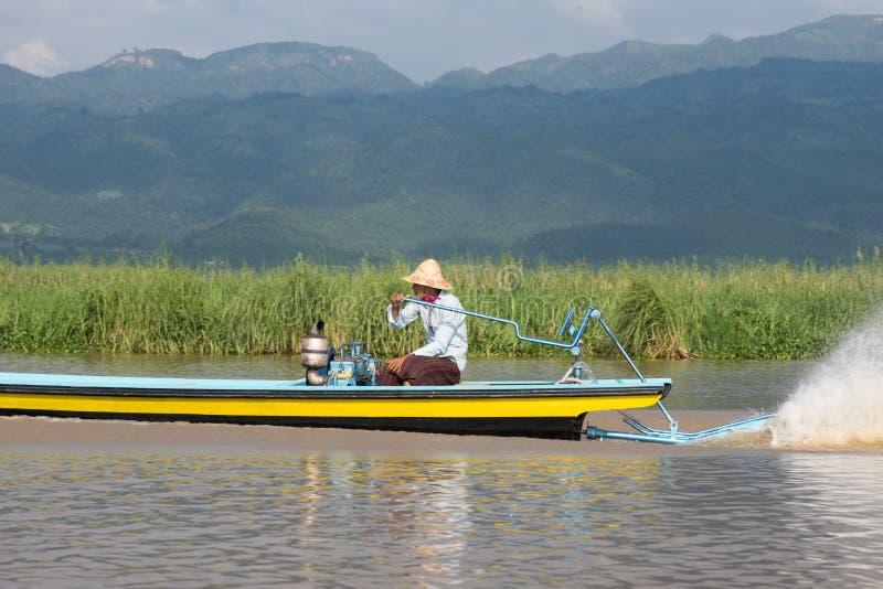 Fiskare som kör i träfartyg på inlesjön i myanmar arkivbilder