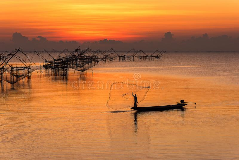 Fiskare som kastar fisknät från hans fartygotta i den sötvattens- sjön av det Phatthalung landskapet, Thailand arkivfoton
