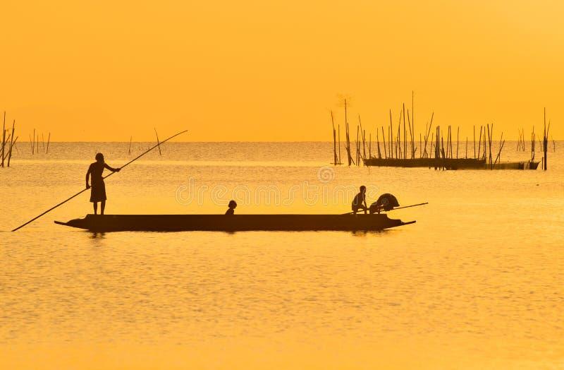 Fiskare som punting hans fartyg, når att ha fiskat i solnedgång på Songkhla sjön, Songkhla, Souhtern av Thailand arkivbild