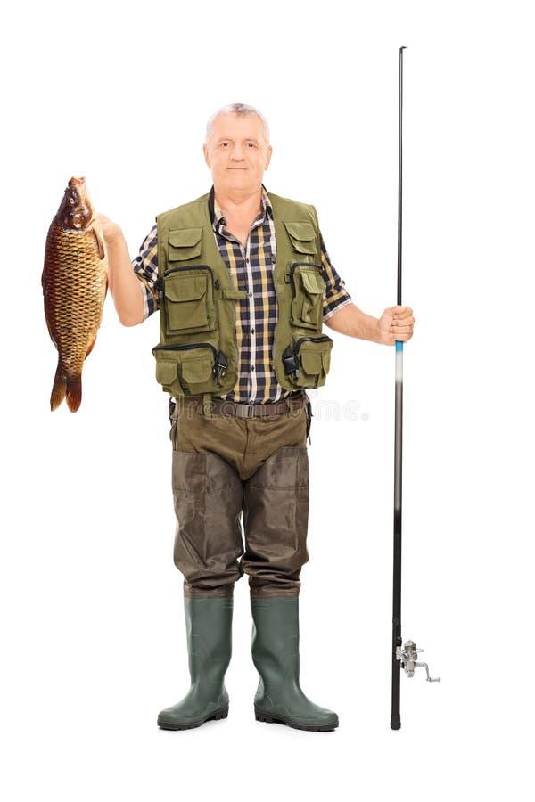 Fiskare som rymmer en fisk och en metspö arkivfoton