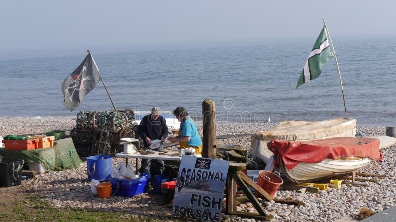 Fiskare som säljer hans lås på en strand i England arkivfoton
