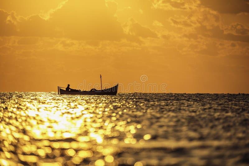 Fiskare som sailling i havet med hans fartyg på härlig soluppgång arkivfoton
