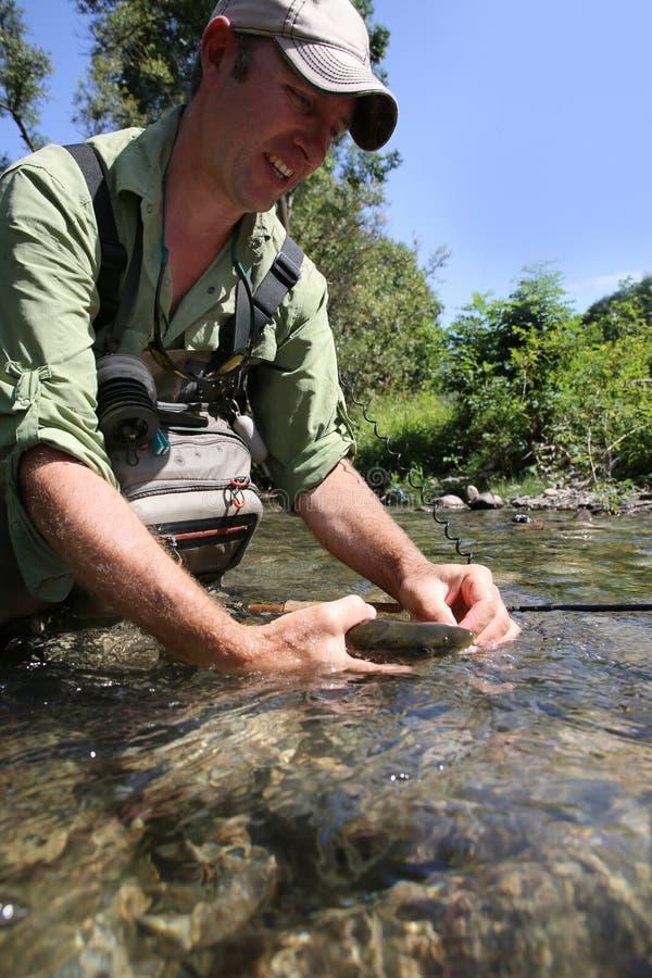 Fiskare som släpper den lilla forellen i floden fotografering för bildbyråer
