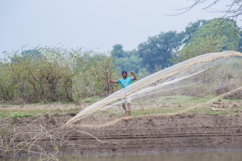 Fiskare Throwing Net i dammet royaltyfri foto
