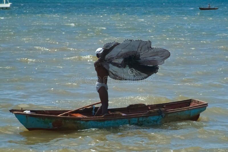 Fiskare Throws ett fisknät vid en fiskebåt royaltyfri fotografi