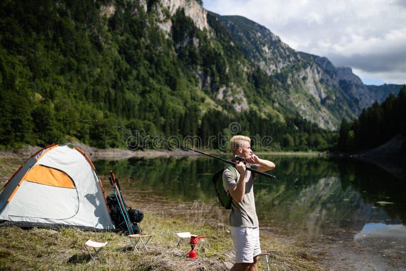Fiskarefiske i natur p? sj?n, medan campa som ?r utomhus- fotografering för bildbyråer