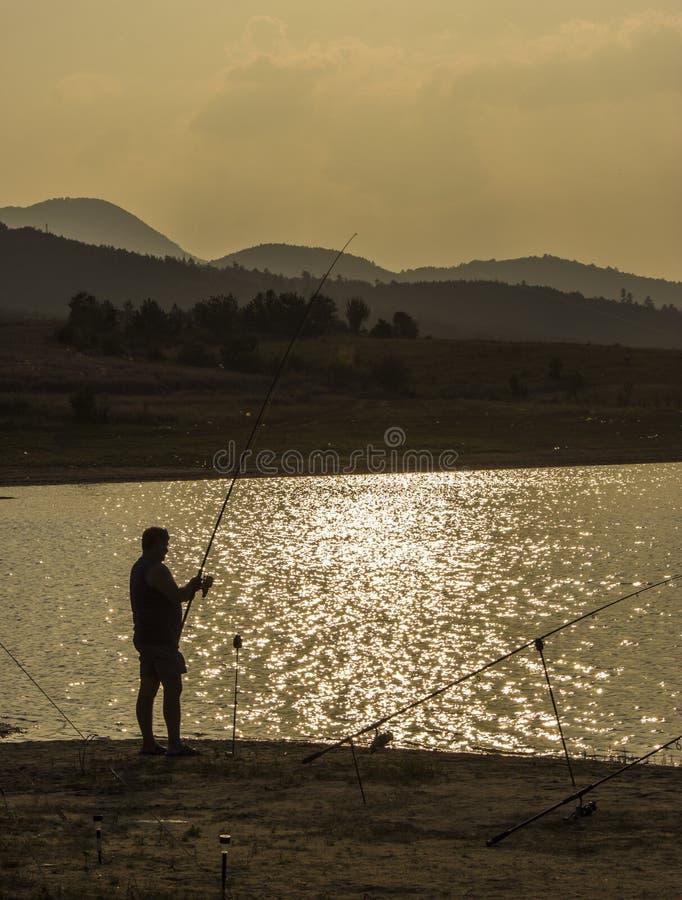 fiskarefiske på solnedgången royaltyfri fotografi