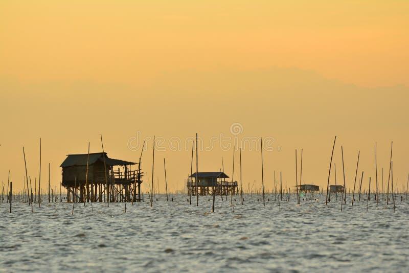 Fiskarehus på havet med bakgrund för skaldjurlantgårdsolnedgång royaltyfri bild
