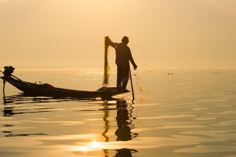 Fiskarelås fiskar för mat i soluppgång i Inle sjön fotografering för bildbyråer