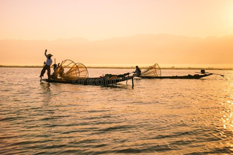 Fiskarelås fiskar för mat i soluppgång i Inle sjön arkivbild