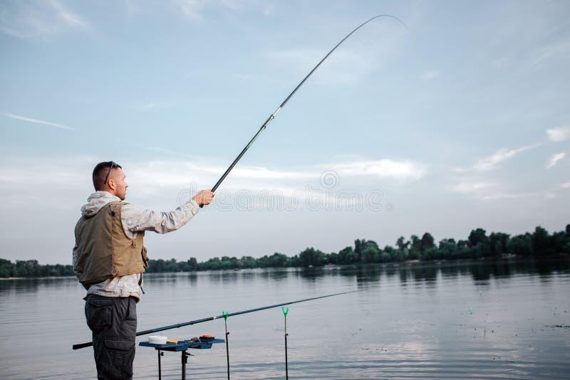 Fiskaren är den stående near klipska stången för watr och för innehavet med assistenten Han har upp det egentligen högt Mannen se royaltyfri bild