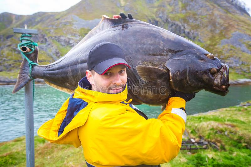fiskaren bär på hans skuldra en enorm fisk 25 kg hälleflundra royaltyfri bild