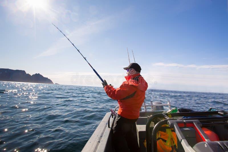 Fiskaren fångar idrottsman nenmitt av havet med fartyg royaltyfri foto