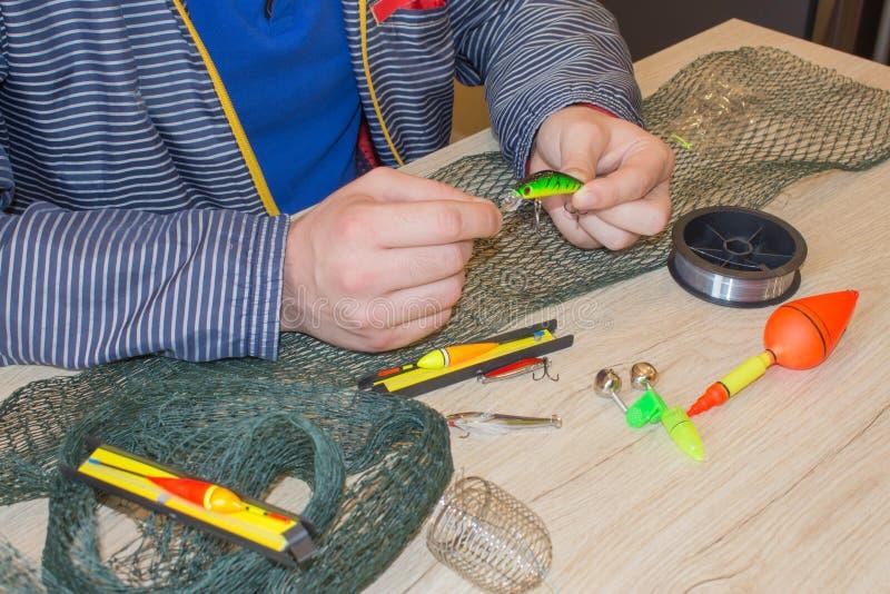 Fiskaren förbereder sig till att fiska Hjälpmedel och tillbehör på trätabellen arkivfoton