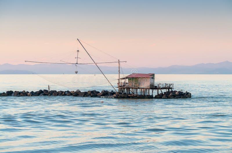 Fiskaren förtjänar längs havet arkivbild