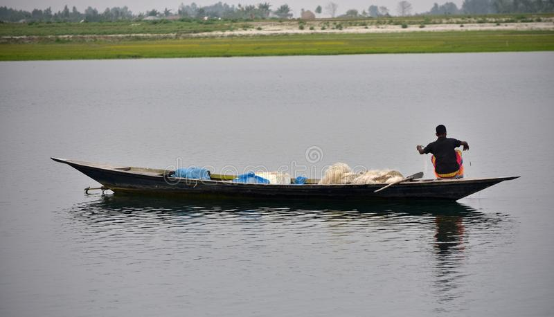 Fiskaren fiskar med hans fartygmaterielfotografi fotografering för bildbyråer