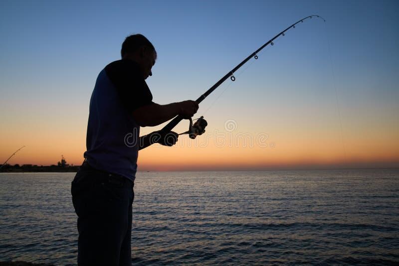 Fiskaren fiskar på royaltyfria bilder