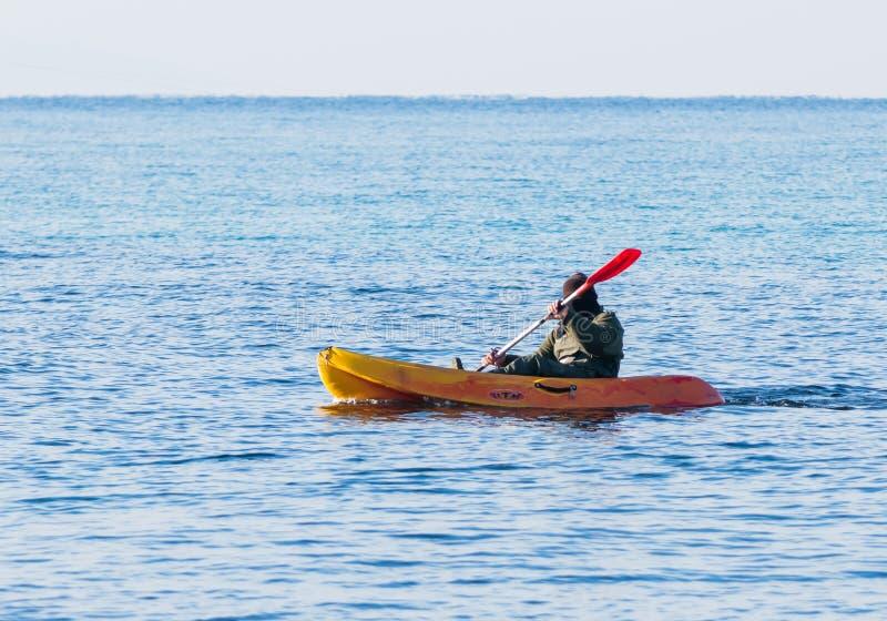 Fiskaren i grön jumpsuit svävar i orange kajak på havet royaltyfri fotografi