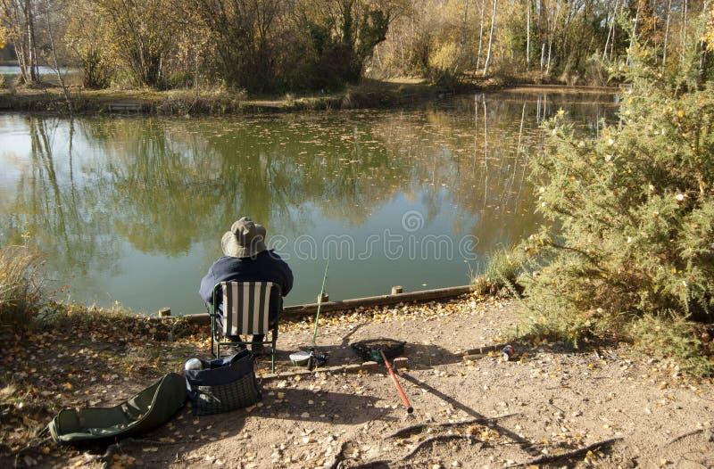 Fiskaren i sjön som sitter på hans stol, skogsmarkvatten, parkerar, Grantham UK royaltyfri bild