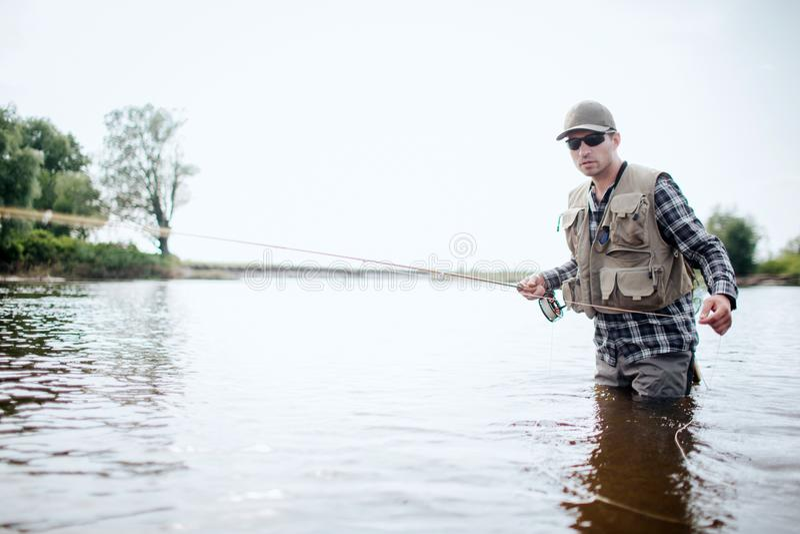 Fiskaren i skyddskläder stnading, i vatten och att fiska Han rymmer fiskstången i en hand och handtagsked med arkivfoto