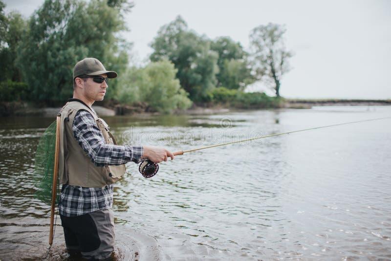 Fiskaren i solglasögon står i vatten Han ser till rätten Grabben har fisknät på baksidan Mannen rymmer flugan arkivbild