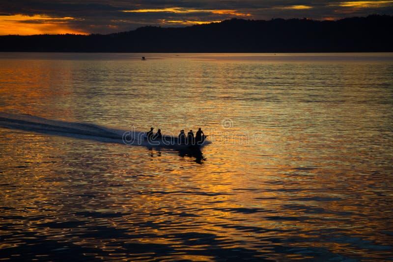 Fiskaren kryssar omkring till havet för att fiska på härlig soluppgång arkivbild