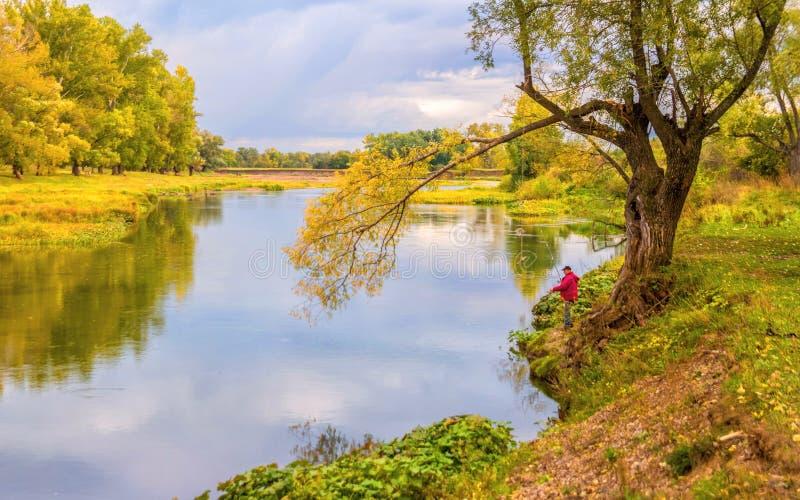 Fiskaren med en metspö står på bankerna av floden i höstskogen royaltyfri bild
