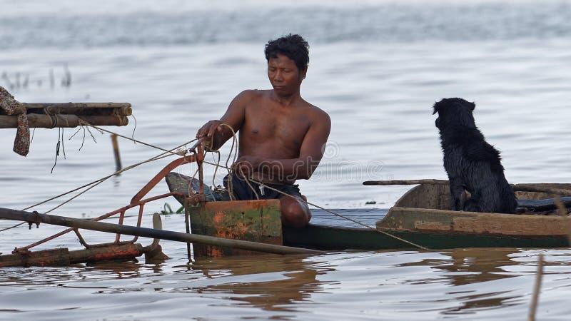 Fiskaren med hunden, Tonle underminerar, Cambodja arkivfoton