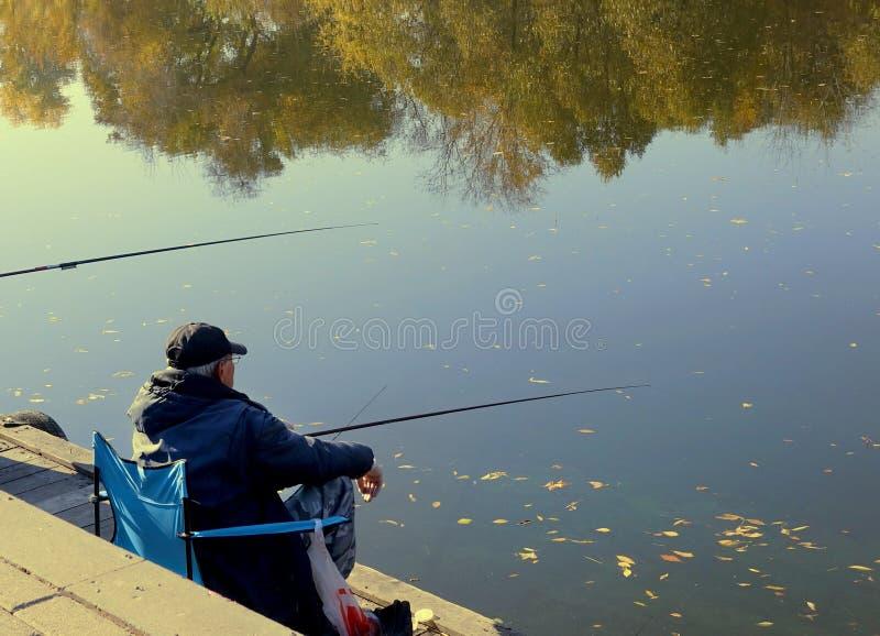 Fiskaren med metspön fångar fisken i en flod som sitter på invallningen royaltyfri bild