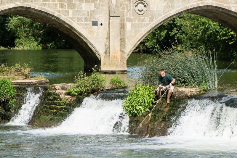Fiskaren på den Bathampton dammbyggnaden med stången och förtjänar royaltyfri foto