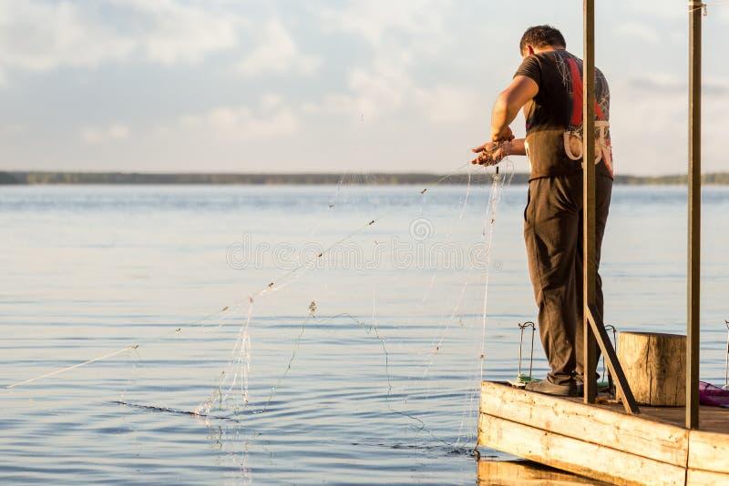 Fiskaren på trä tränger igenom Fiskeman som ut netto tar från vatten skjuten solnedgångtid för exponering long Copyspace royaltyfri fotografi