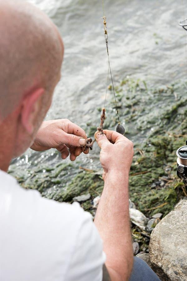 Fiskaren rymmer en krok och avmaskar royaltyfria bilder