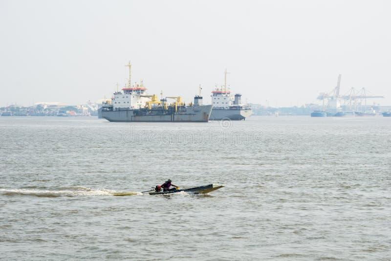 Fiskaren seglar fartygpasserandet för den långa svansen till och med sandgrävareskepp i den Chao Phraya floden arkivfoto