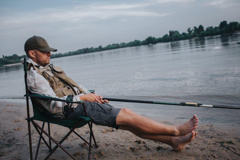Fiskaren sitter, i hopfällbar stol och att sova Hans lock ligger på ögon Mannen rymmer den klipska stången i händer Han fiskar royaltyfri foto