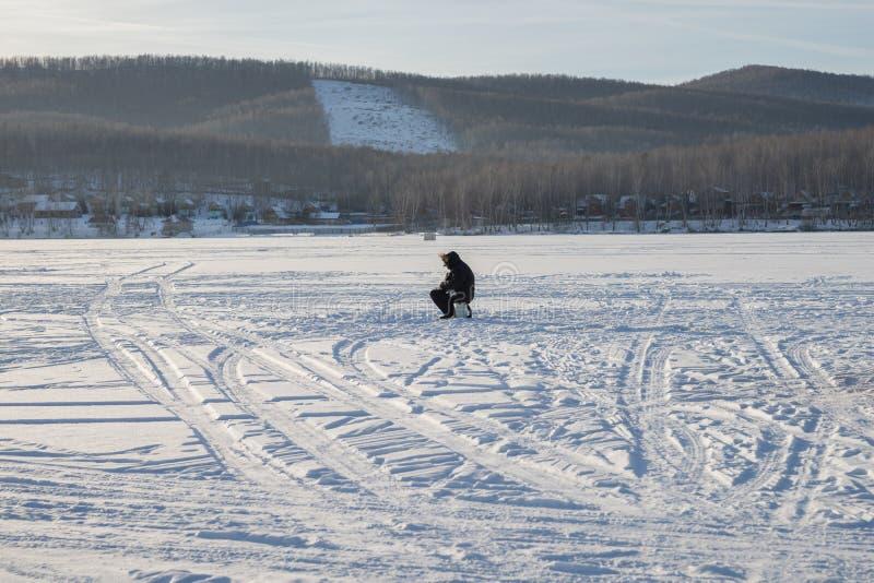 Fiskaren sitter, och lås fiskar på den snöig sjön, i aftonen royaltyfri foto