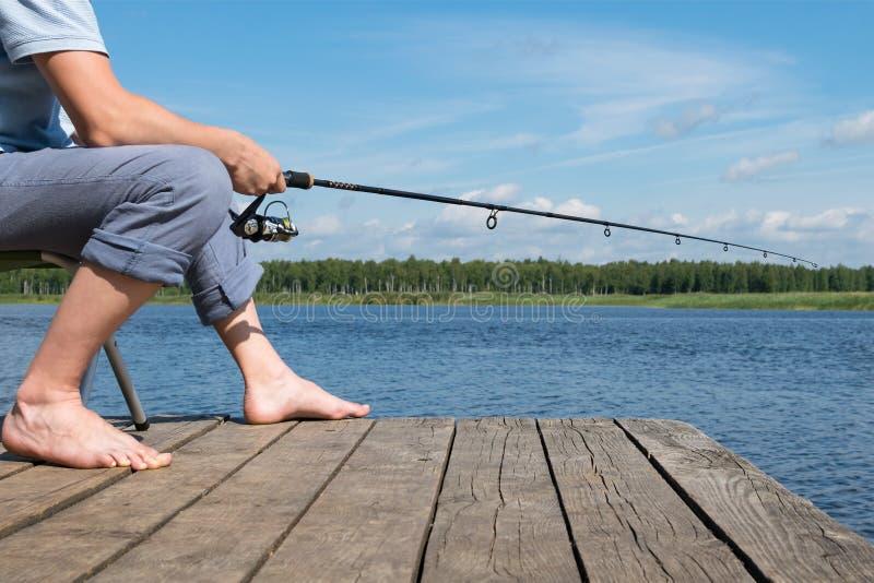 Fiskaren sitter på en stol och fångar fisken från pir på betet arkivbilder