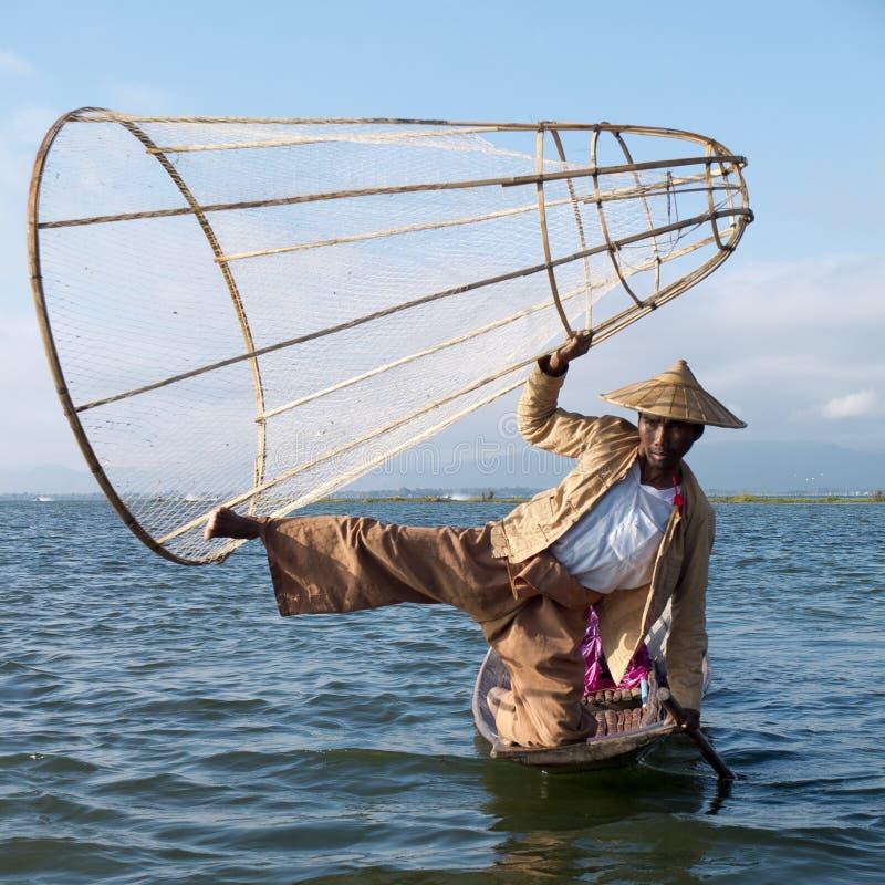 Fiskaren som rymmer det traditionella koniskt, förtjänar royaltyfri bild