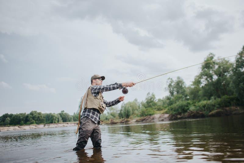Fiskaren står, i grunt och att fiska Han kastar den framåt skeden för den Grabben rymmer den klipska stången i händer Han är royaltyfri foto