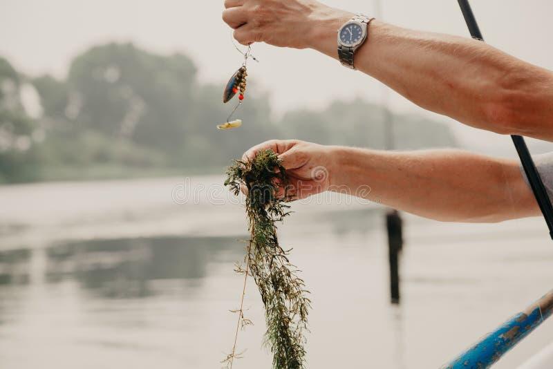 Fiskaren tar bort alger från metspöet på fartyget royaltyfria bilder